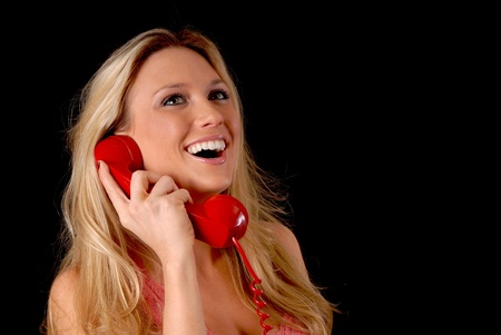 telephone: Isolated lovely and sexy young blond girl talking on a telephone