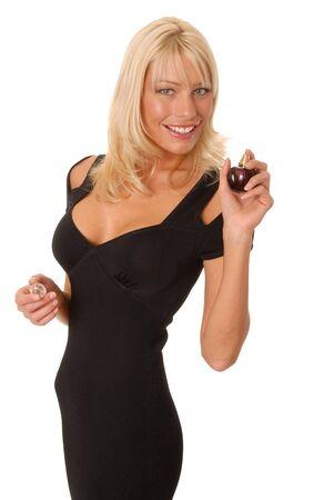 Lovely blond girl appling perfume from a perfume bottle
