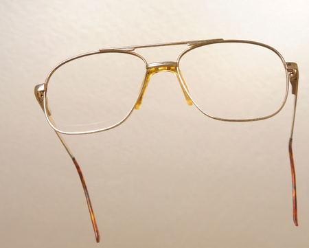 opthalmology: Modern medical eyeglasses isolated on a tan background
