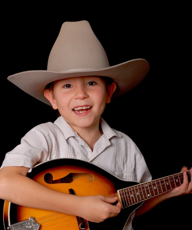 Young boy wearing a cowboy hat isolated on black playing the mandolin photo