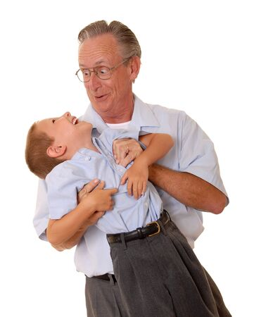 family tickle: Father lifting son having fun over white