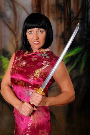Isolated lovely and sexy young brunette dancing girl holding a sword photo