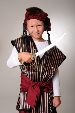 cutlass: Boy Pirate isolated on gray with a cutlass Stock Photo