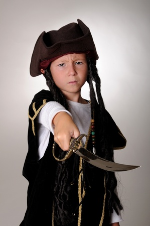 cutlass: Boy Pirate isolated on black with a cutlass