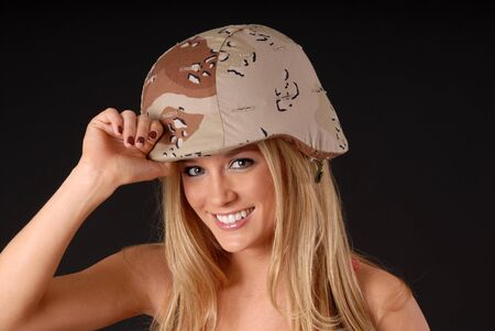 Isolated lovely and sexy young blond girl wearing army  helmet photo