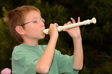 flute instrument: Young boy playing a recorder musical instrument