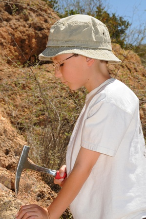 paleontologist: Boy geologist tap a rock formation with a hammer