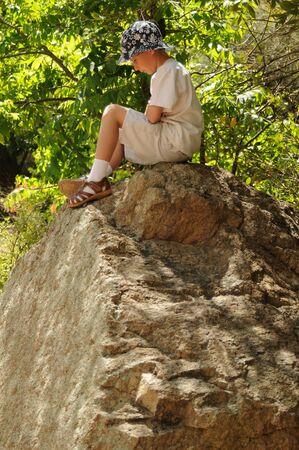 큰 둥근 돌 위에 혼자 앉아있는 소년
