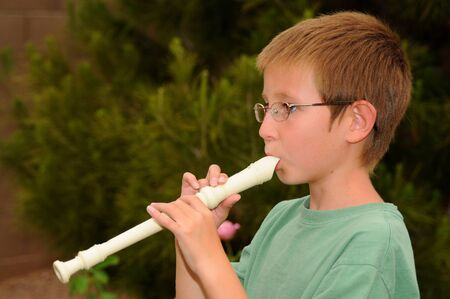 flute key: Young boy playing a recorder musical instrument