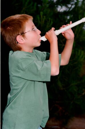 Young boy playing a recorder musical instrument photo