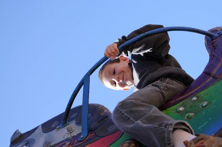 Young boy playing on a carnival ride photo