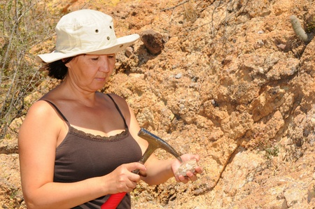 paleontologist: Senior woman geologist tap a rock formation with a hammer