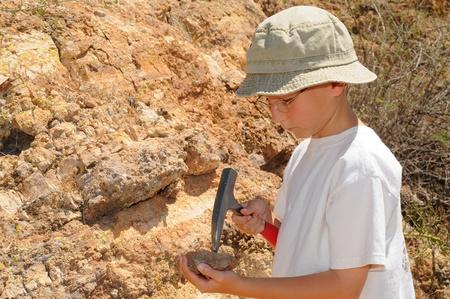 Giovane ragazzo studiando geologia fuori nel campo