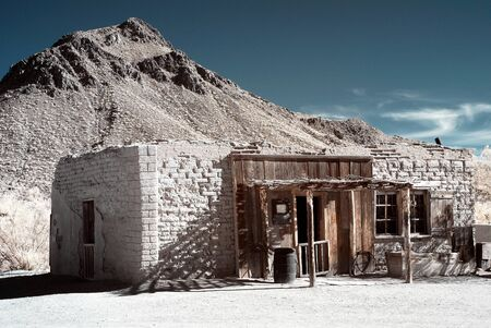 Old style western adobe building mountain background photo