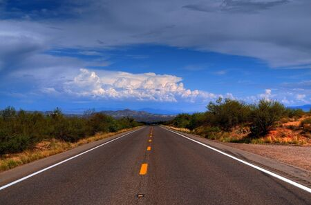 Dramatic desert mountain road with a storm approaching photo