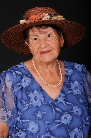 A senior woman portrait isolated over black photo