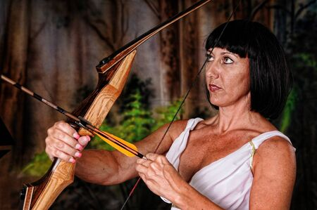 Tough brunette girl with bow and arrow