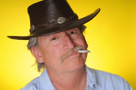Old senior cowboy smoking a hand rolled cigarette Stock Photo - 9724498