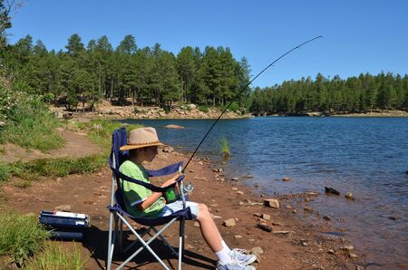 Young boy fishing and resting in a chair photo