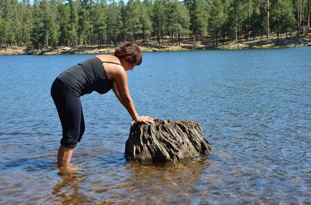 Woman in a lake resting on a stump photo
