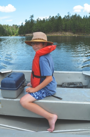 Young boy wearing life vest piloting a small boat photo