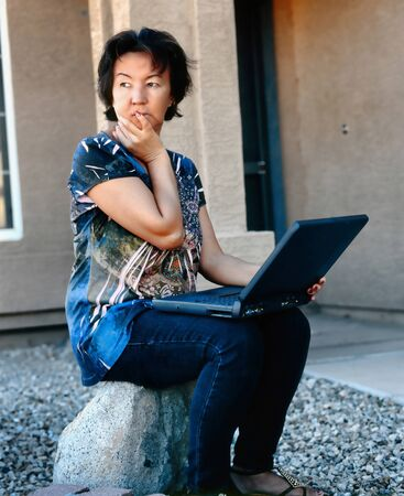 Woman sitting outdoors with a laptop computer photo