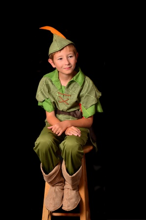Young boy dressed as Peter Pan sitting on a stool Banco de Imagens