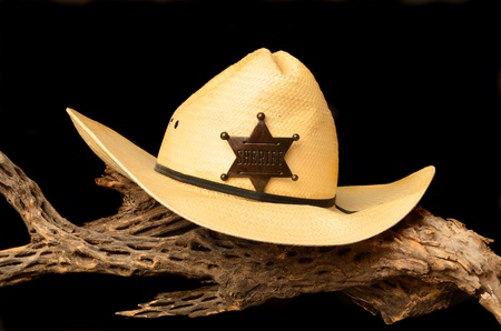 sheriffs: Cowboy hat and sheriffs badge isolated over black