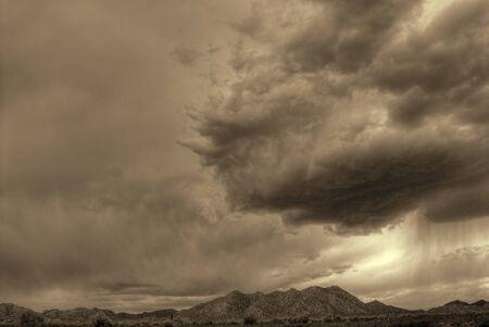 Sepia tone desert storm forming over Arizona Mountains