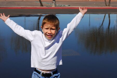 Worried looking boy running with his arms out Stock Photo