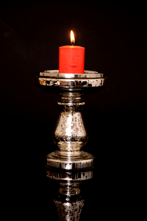 candle holder: Lighted red candle in a candle holder