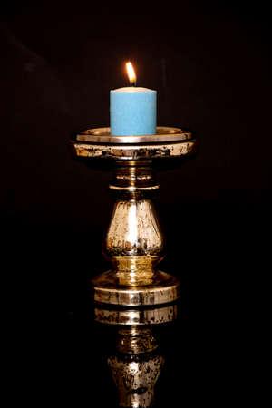 Lighted candle and cadlestick holder over black