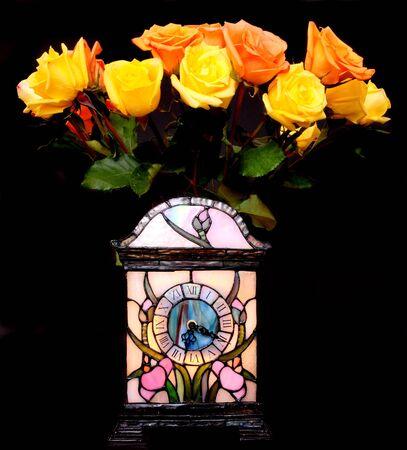 Geel en perzik rozen en klok over zwarte