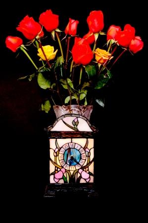 Rode en gele rozen en klok over zwarte Stockfoto