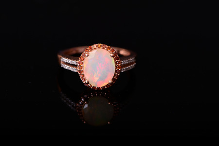 Opal and diamond gold ring isolated over black