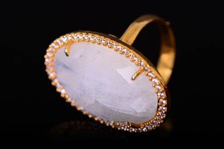 Moonstone and gold diamond ring isolated over black