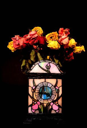 perish: Clock and dead flowers perish with time Stock Photo