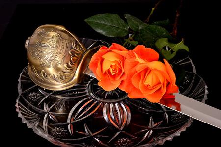cutlass: Cutlass y rosas aislados sobre un fondo negro Foto de archivo