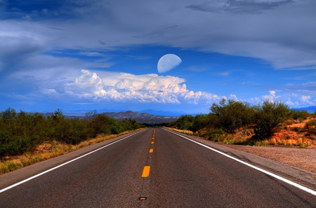 Dramatic desert mountain road with moon and storm approaching photo