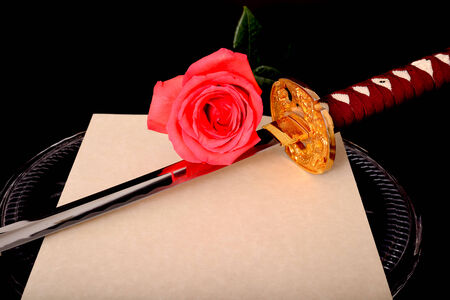 Quill parchment sword and rose isolated over black Stock Photo