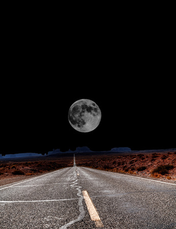 Dramatic desert mountain road with full moon Banco de Imagens