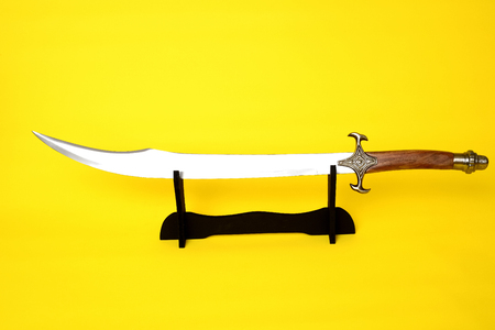 scimitar: Scimitar blade, guard, and hilt isolated over blue