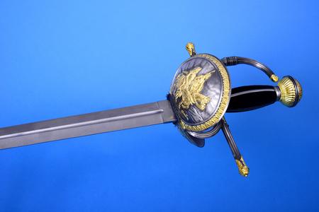 hilt: Rapier sword blade, guard, and hilt isolated over blue