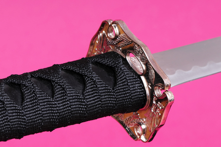 hilt: Japanese sword blade, guard, and hilt isolated over pink