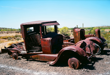 corroding: Broken down and rusty old trucks with no tires in the desert Stock Photo
