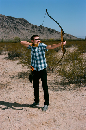 Young man shooting a bow and arrow in the desert Фото со стока