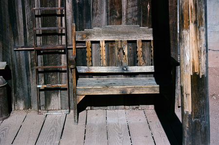 Old rustic wooden bench on a wooden sidewalk, bucolic  Фото со стока