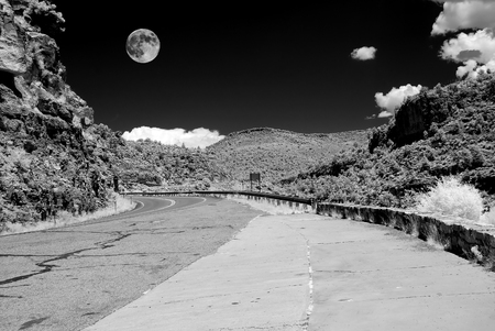 Infrared monochrome desert full moon over the southwestern USA Sonora desert Arizona and mountain road