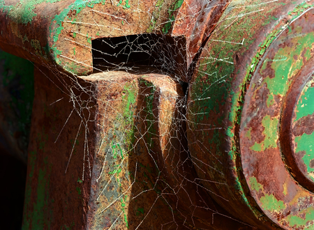 Abandoned Rusty mining iron wheel with old flaking paint and cobwebs