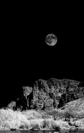 Infrared monochrome desert moon over the southwestern USA Sonora desert Arizona and mountains Stock Photo